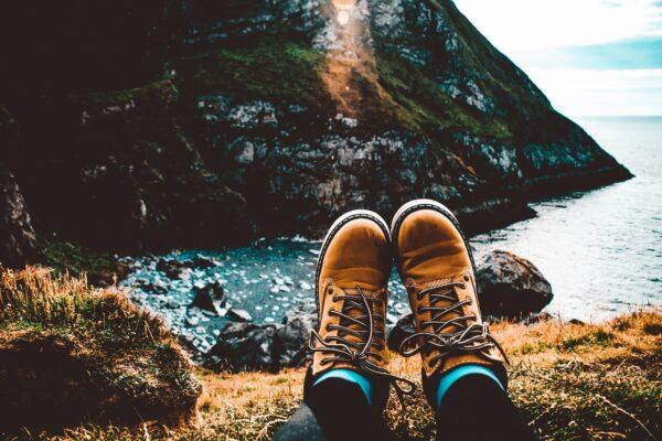 Brune støvler der hviler på sten ved kyst