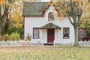 Hvidt og rødt hus står i bland træer