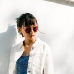 Kvinde har hvid jakke på og solbriller
