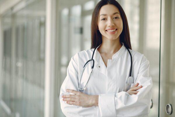 Læge smiler med stetoskop om halsen